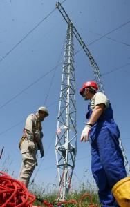 O echipa de electricieni specializata in lucrari sub tensiune a societatii Smart SA efectueaza o reparatie la izolatorul unui stalp de inalta tensiune apartinand societatii Transelectrica